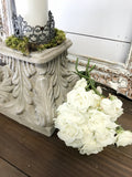 concrete pedestal with candle and white roses