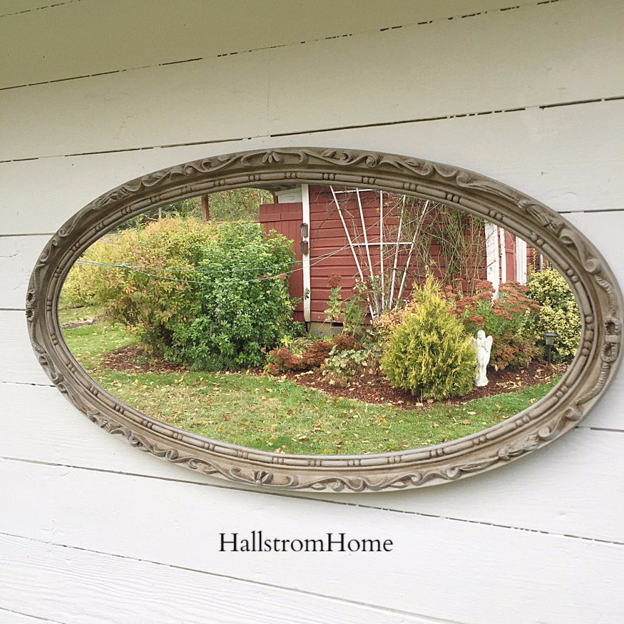 ornate oval mirror hanging on white whall