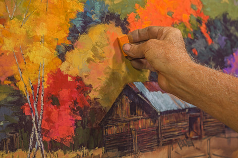 A hand with a piece of chalk pastel adding orange shading to a cabin in fall surrounded by foliage