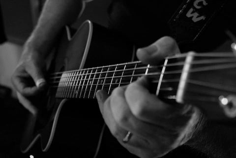 Close up of man playing acoustic guitar