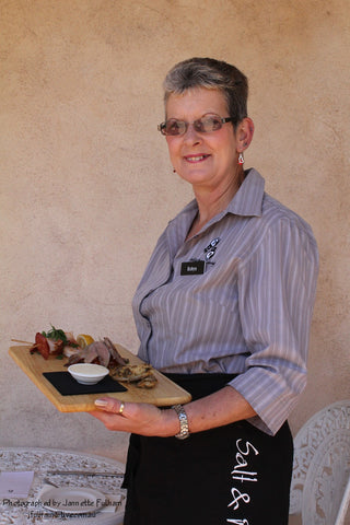 Salt and Pepper Catering waitress holds platter of food