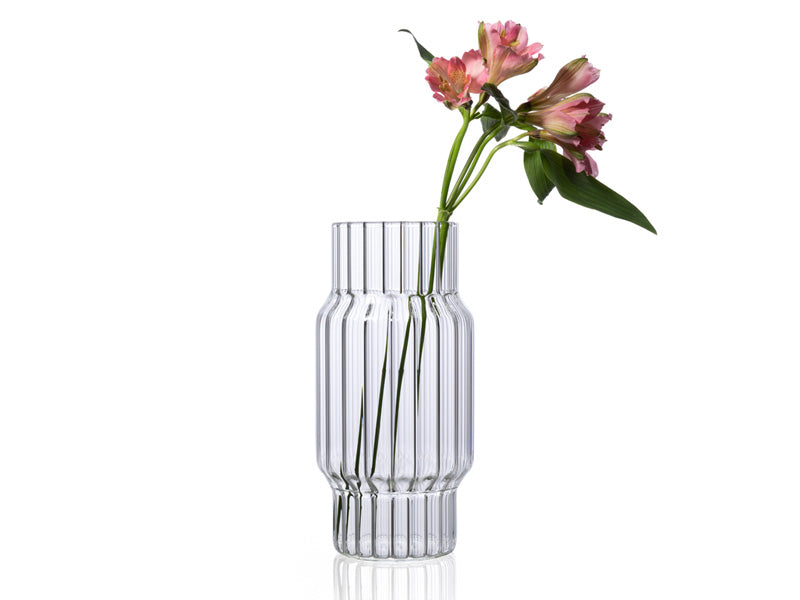 Clear, large, fluted glass vase with flower for home decor.