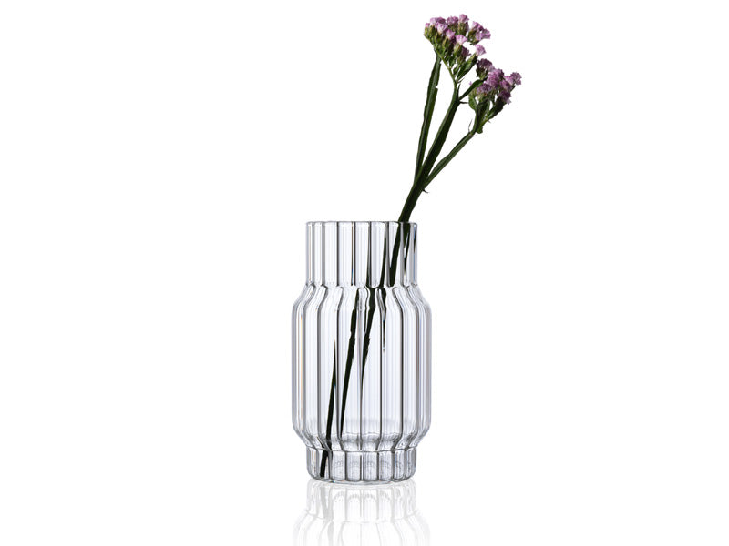Clear, fluted, glass vase with flower for home decor.