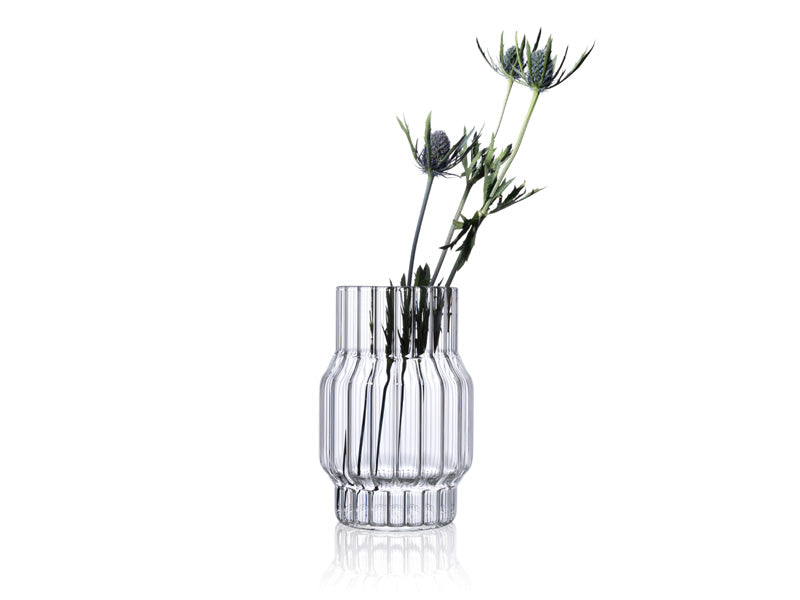 Small designer vase in fluted glass with flowers for home decor.