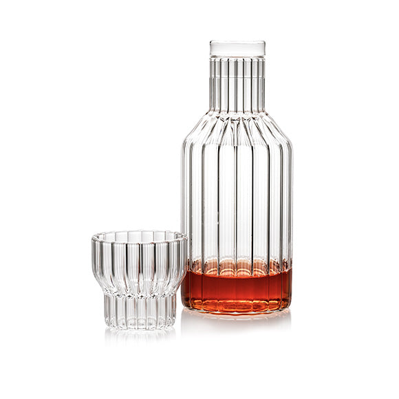 A modern, designer decanter or bedside carafe in fluted glass with a small fluted drinking glass. Sold as a set.