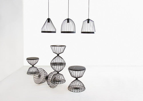 Hanging bird cage lamps above metal and marble tables.