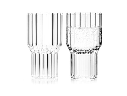 A pair of fluted, contemporary, clear glasses by designer, Felicia Ferrone. One glass is filled with carbonated water, the other is empty.