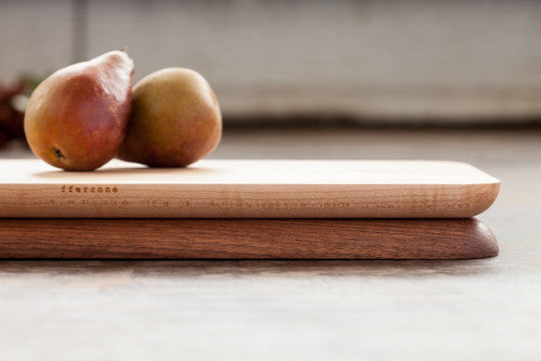 Maple side up on a rectangular cutting board composed of walnut and maple, styled with two pears.