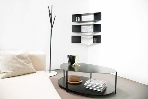 Two tiered black metal table in a room with metal corner shelves and coat tree, all by designer, Felicia Ferrone.