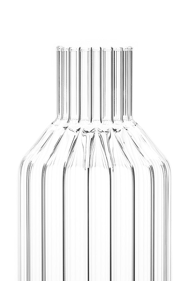 A close-up of a designer decanter in fluted glass without lid on.