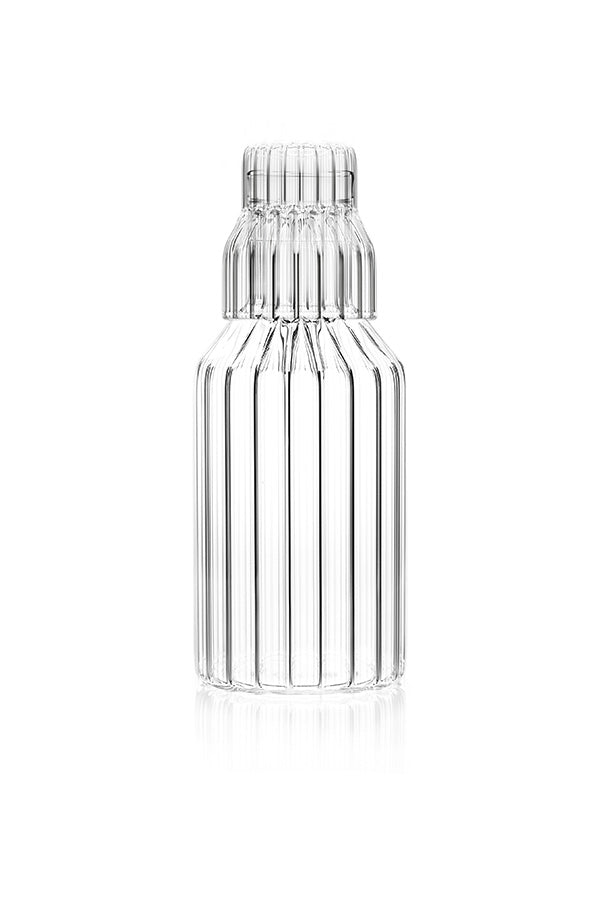 A handmade, fluted glass carafe by contemporary designer with small fluted glass.