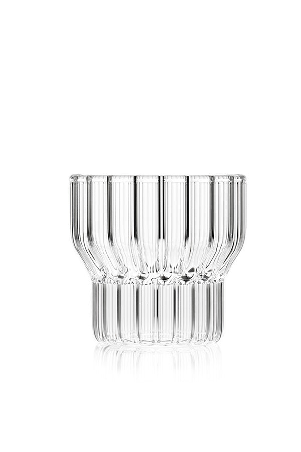 A single low, clear, fluted drinking glass by contemporary designer.