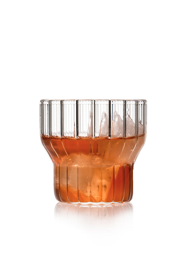 A low, fluted, modern drinking glass filled with ice cubes and amber drink.
