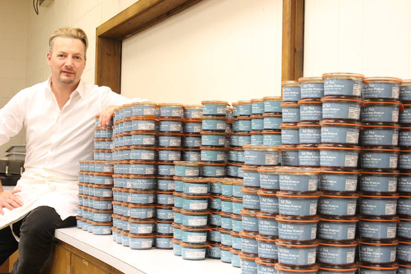 Gino De Schrijver sitting down next to a mountain of Eat This jam, jelly, and preserves.