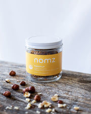 hazelnut vegan energy balls in a sustainable glass jar with dry roasted hazelnuts