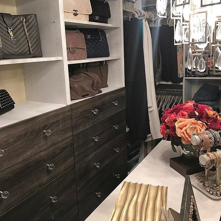 Grey closet with drawers and shelves displaying handbags