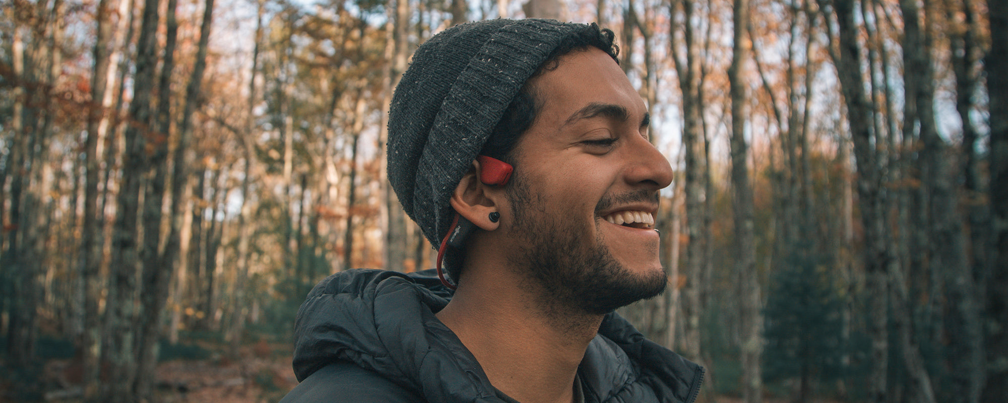 Man outside in forest wearing AfterShokz Air headphones