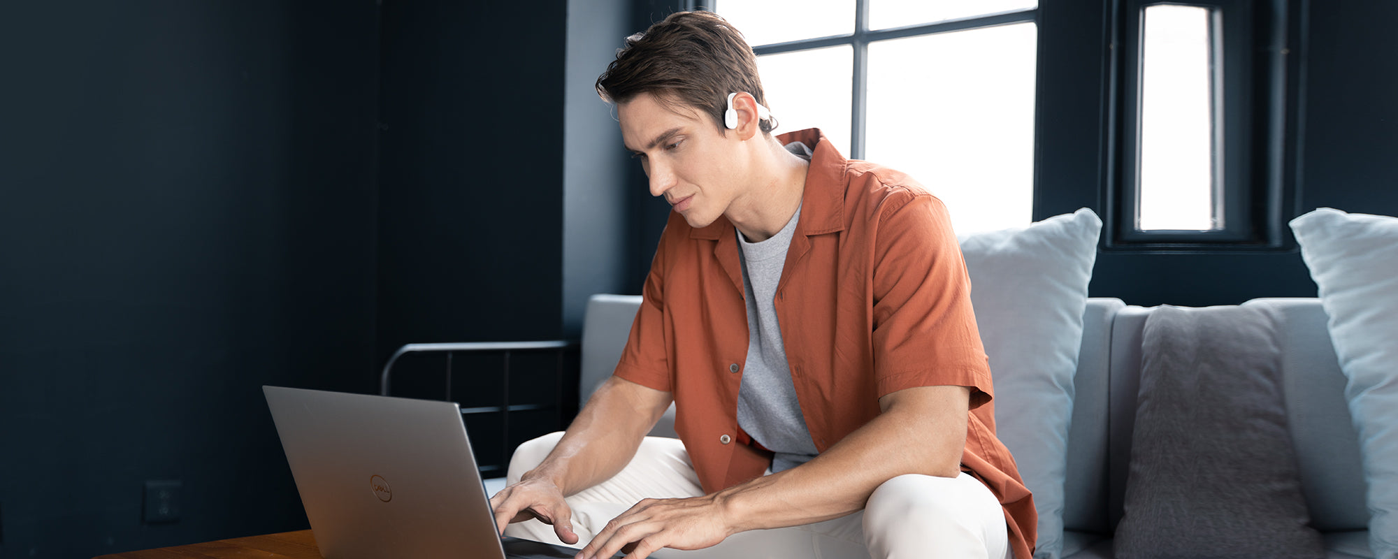 Man on laptop while wearing AfterShokz OpenMove headphones