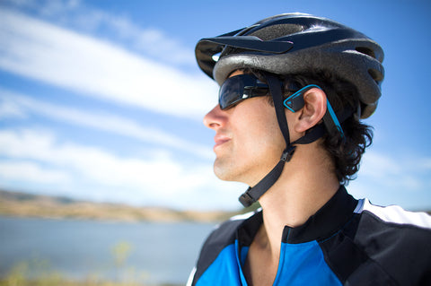 Male cyclist wearing blue bone conduction headphones under bike helmet