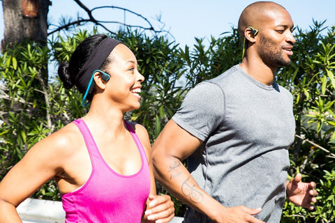 A man and woman out jogging wearing bone conduction headphones