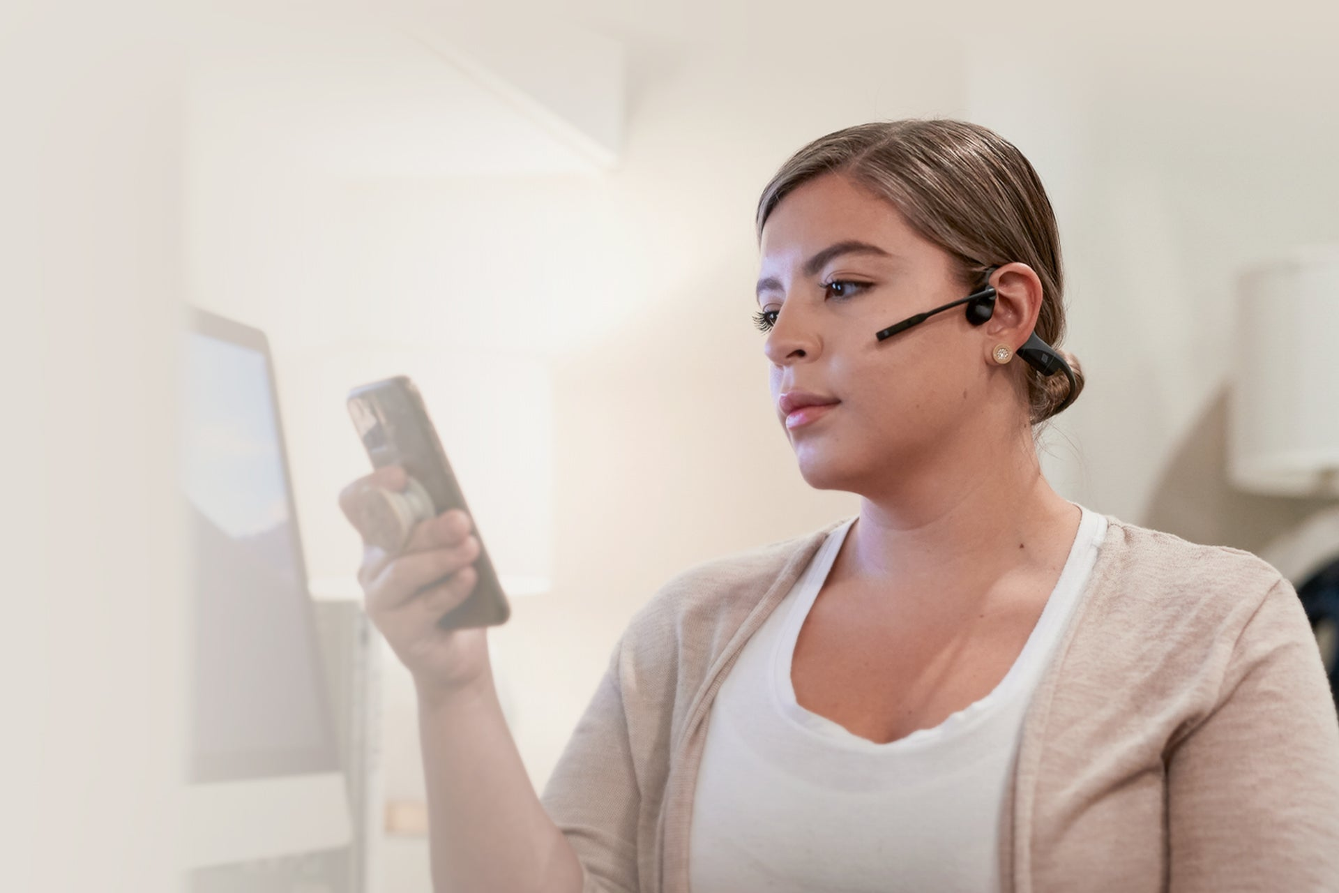 Woman using mobile phone while wearing AfterShokz OpenComm headset