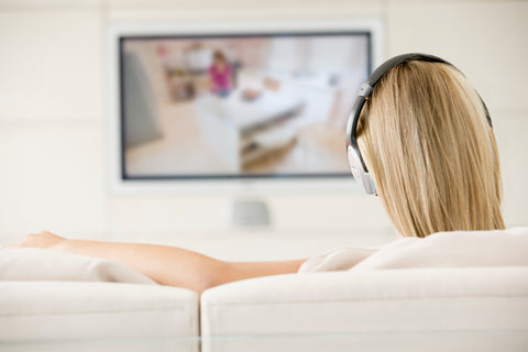 The back of a woman's head as she sits on the couch watching TV with full sized headphones