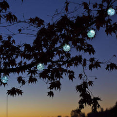 A string of hand-blown glass, solar-powered lantern lights by Allsop Home & Garden, glowing blue hung on tree.