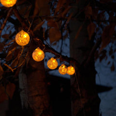 A string of hand-blown glass, solar-powered lantern lights by Allsop Home & Garden, glowing yellow hung on tree.