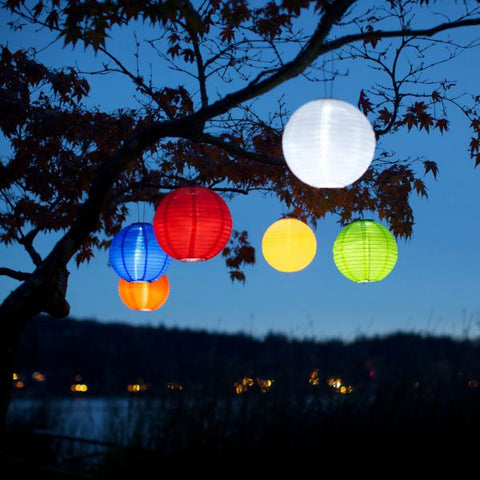 Allsop Home & Garden Soji Original Solar Lanterns in a variety of bright colors hang in a tree together at night.