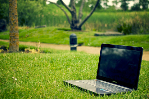 Laptop on green grass to do green business