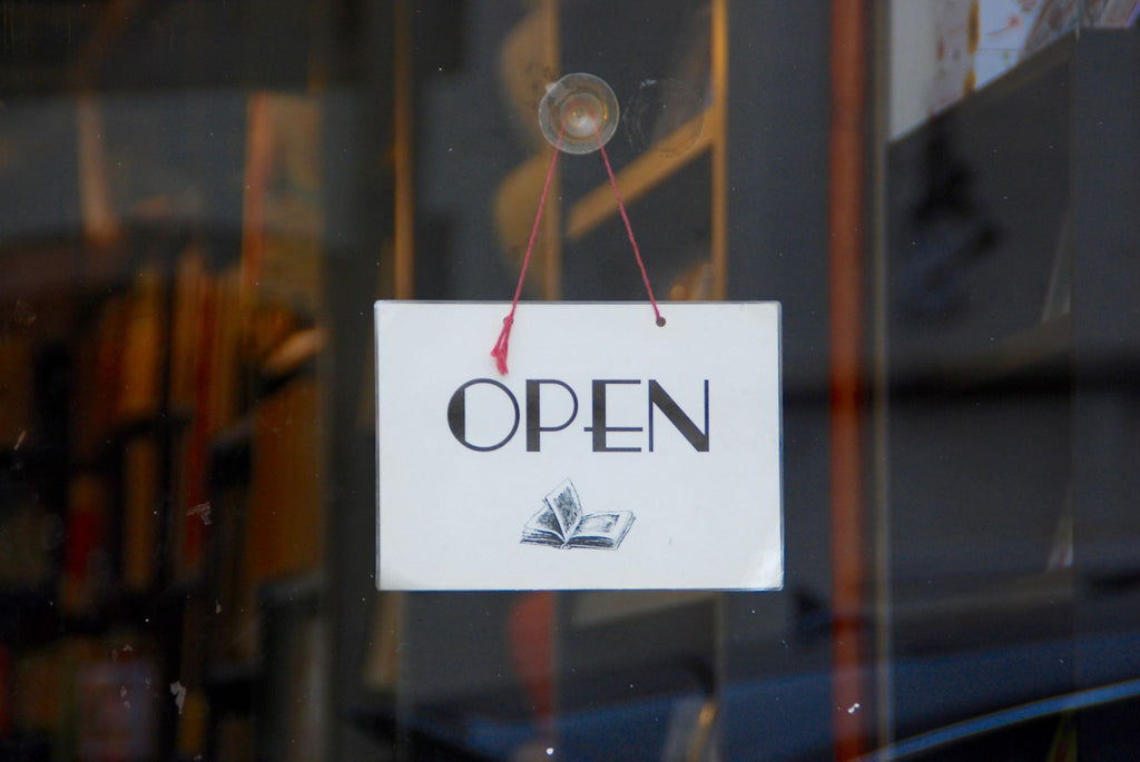 "Cute ""Open"" sign with bold font hanging on front door of local bookstore"