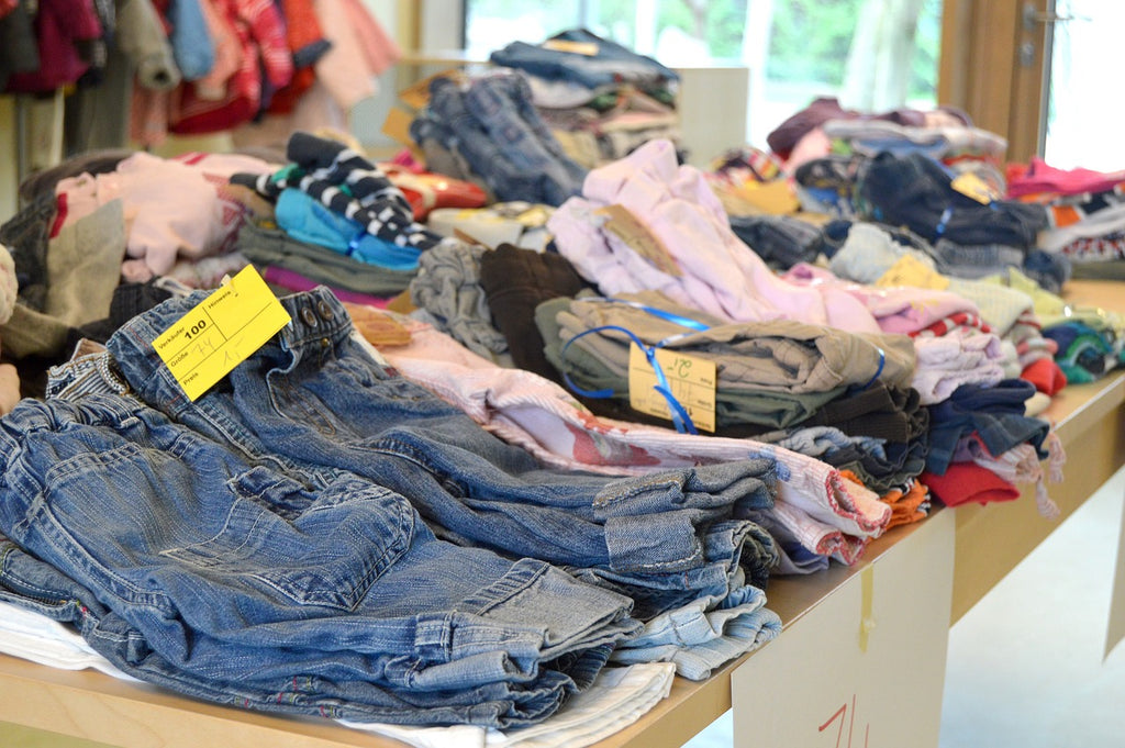 A table of folded jeans sold secondhand at a flea market