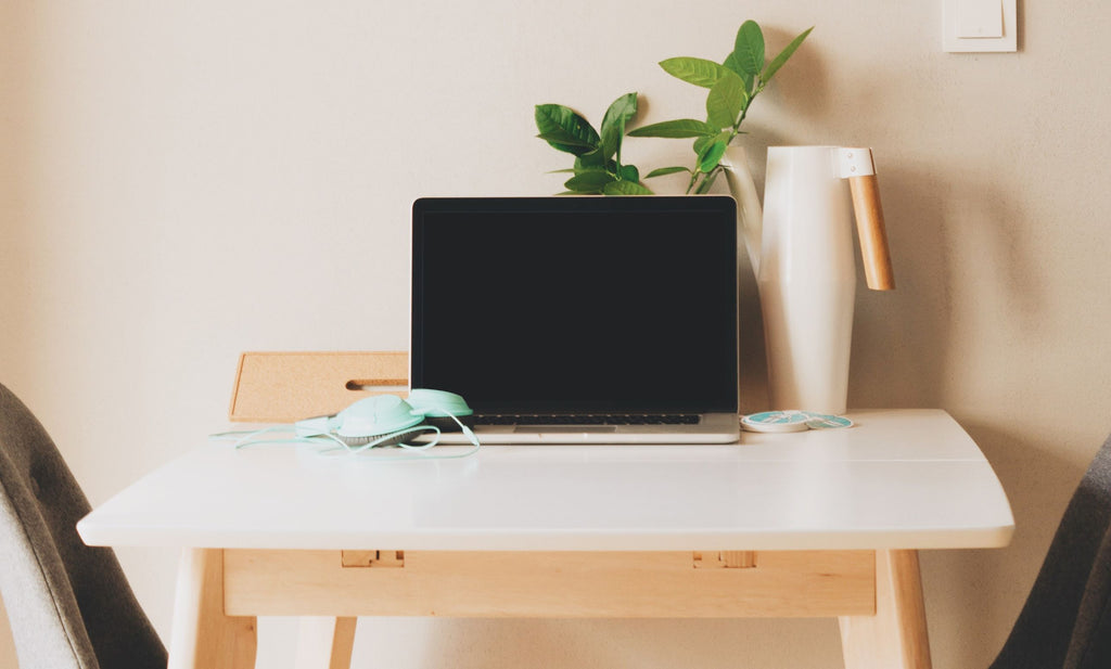 Macbook, headphones and plant sit atop a simple, uncluttered desk.