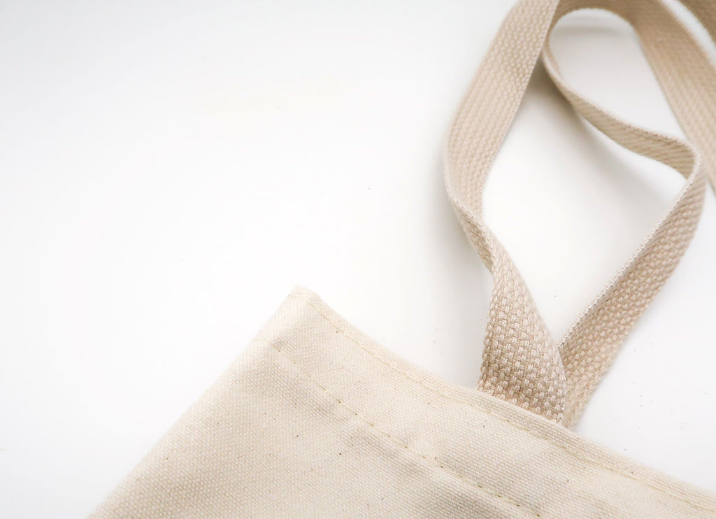 Close-up of white canvas tote bag strap, a reusable alternative to plastic