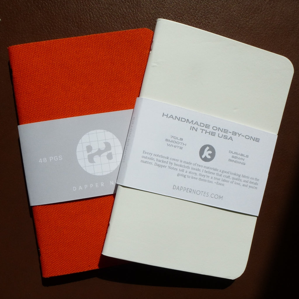 two notebooks, one white, one orange