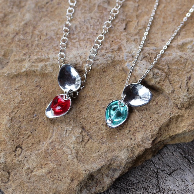 2 sterling leaf locket pendants open so the red and blue glass hearts are visible.