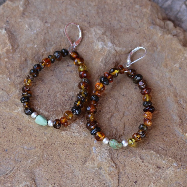 Flexible hoop earrings with amber beads and a single turquoise bead framed with sterling silver beads. Sterling silver lever back ear wires.