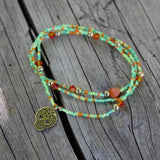 Stretch necklace or triple wrap bracelet with bronze sugar skull and pastel green bead mix
