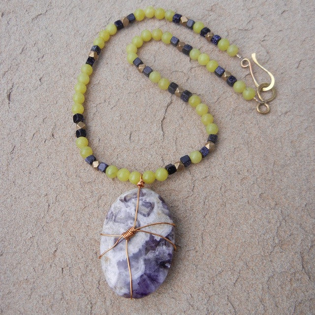 Bold wire-wrapped amethyst pendant necklace with green serpentine and blue goldstone and a brass hook clasp