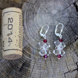 Clear crystal barbell shaped beaded earrings with ruby-colored Swarovski crystals and sterling lever back ear wires. Cork for size reference