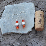 Sterling laser-cut bead earrings with orange Swarovski crystals. Intricate swirling patters are laser cut into the surface of the sterling beads which are framed with orange Swarovski crystals. Cork for size reference.