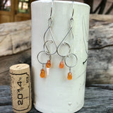 Sterling silver wire swirls earrings with carnelian drops. Cork for size reference