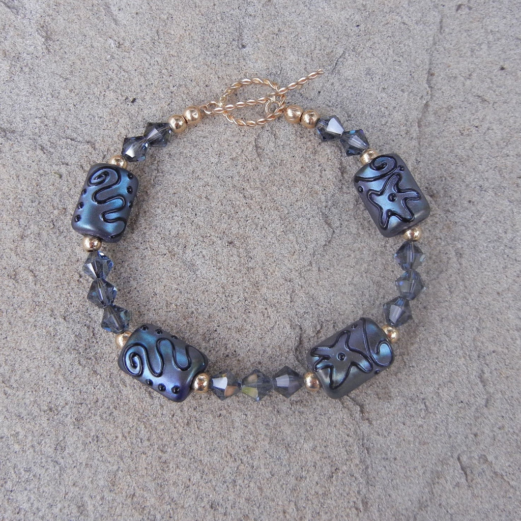 Blue artisan glass bead bracelet with Swarovski crystals and gold filled bead accents and toggle clasp