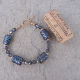Blue artisan glass bead bracelet with Swarovski crystals and gold filled accent beads. Cork for size reference