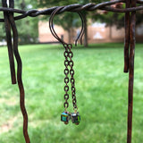 Long bronze chain earrings with Swarovski crystal cubes hanging from fence wire.