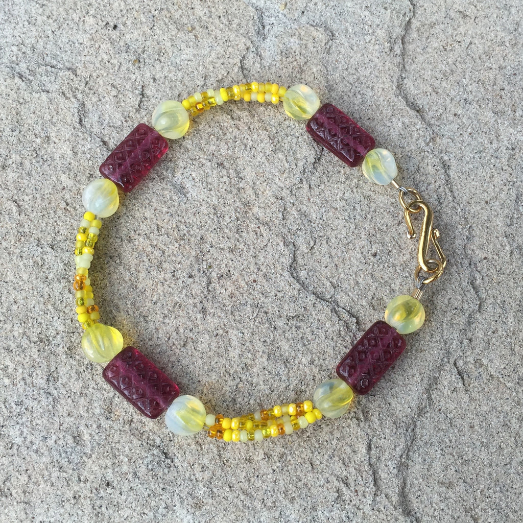 Bracelet with 3 strands of yellow mix seed beads and deep red rectangular glass beads with gold filled clasp