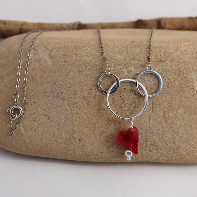 Sterling silver chain necklace with interlocking circles and red Swarovski heart pendant