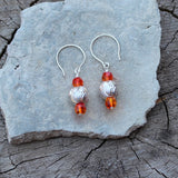 Sterling laser-cut bead earrings with orange Swarovski crystals. Intricate swirling patters are laser cut into the surface of the sterling beads which are framed with orange Swarovski crystals.