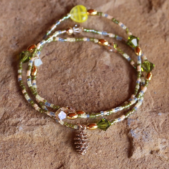 Stretch necklace or triple wrap bracelet with bronze pine cone charm and green, pink and blue seed beads