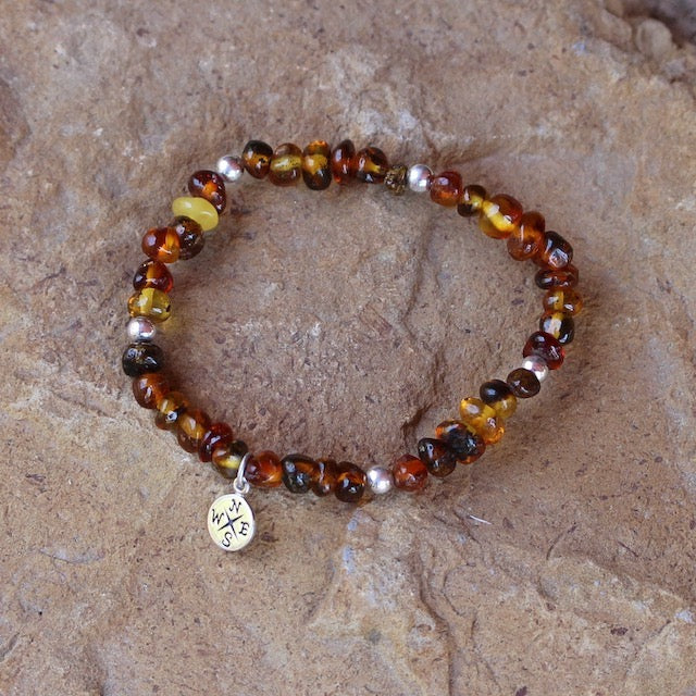 Amber nuggets stretch bracelet with sterling silver compass charm.